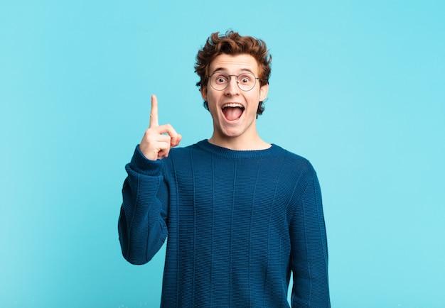 Giovane bel ragazzo che si sente un genio felice ed eccitato dopo aver realizzato un'idea, alzando allegramente il dito, eureka!