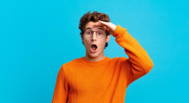 Giovane bel ragazzo che sembra felice, stupito e sorpreso, sorride e realizza buone notizie incredibili e incredibili