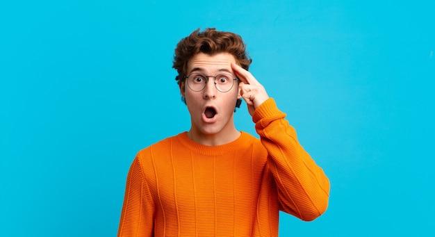 Giovane bel ragazzo che sembra sorpreso, a bocca aperta, scioccato, realizzando un nuovo pensiero, idea o concetto