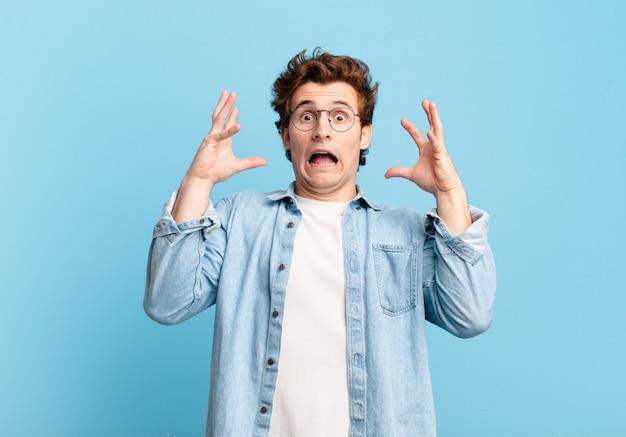 Giovane bel ragazzo che urla con le mani in aria, sentendosi furioso, frustrato, stressato e turbato