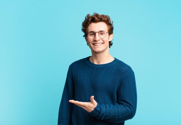 Giovane bel ragazzo che sorride allegramente, si sente felice e mostra un concetto nello spazio della copia con il palmo della mano