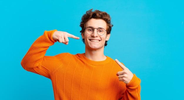 Giovane bel ragazzo che sorride con sicurezza indicando il proprio ampio sorriso, atteggiamento positivo, rilassato e soddisfatto