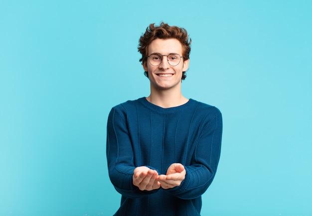 Giovane bel ragazzo che sorride felicemente con uno sguardo amichevole, fiducioso e positivo, offrendo e mostrando un oggetto o un concetto