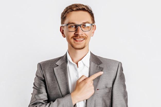 Giovane uomo bello brunet in bicchieri in tuta punta il dito a lato su sfondo bianco isolato