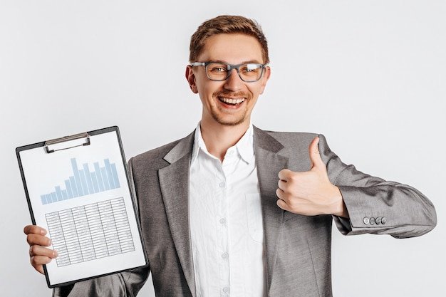 Giovane uomo bello del brunette in vetri in un vestito sorride e mostra i pollici in su con documenti aziendali e grafici su sfondo bianco isolato