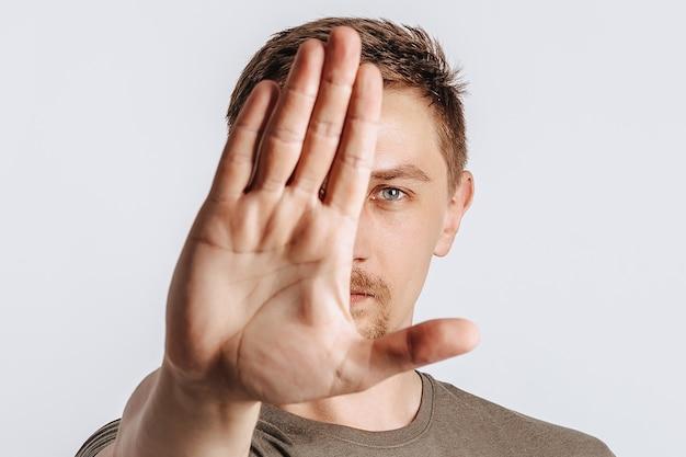 Il giovane uomo bello del brunette ha allungato la sua mano in avanti stop su sfondo grigio isolato