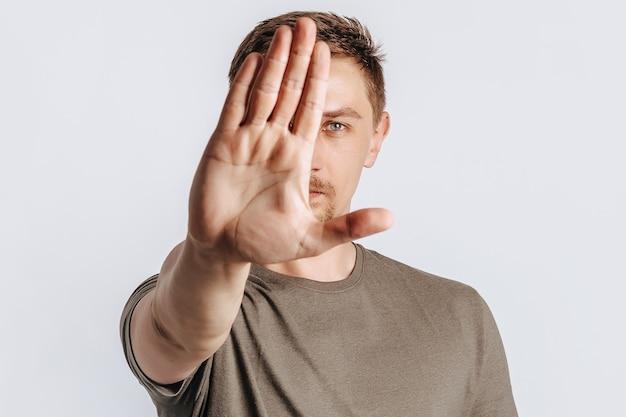 Il giovane uomo bello del brunette con la barba stese la mano in avanti e dice stop su sfondo bianco isolato