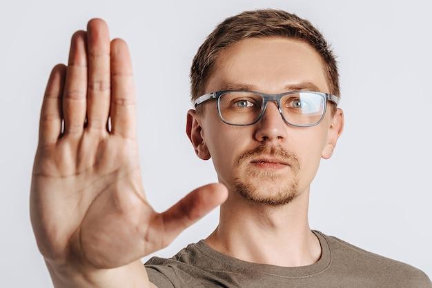 Il giovane uomo bello del brunette con la barba che indossa gli occhiali ha allungato la mano in avanti e dice stop su sfondo bianco isolato