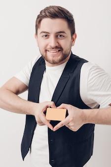 Giovane bell'uomo bruna con la barba in una camicia bianca e un gilet nero in possesso di una carta di credito in plastica e sorridente. luce soffusa