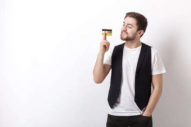 Giovane bell'uomo bruna con la barba in una camicia bianca e un gilet nero che mostra una carta di credito di plastica e sorride