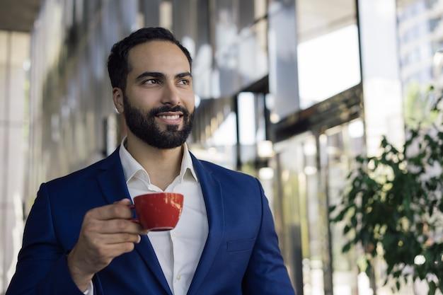 Giovane uomo bello di affari che beve caffè nella caffetteria