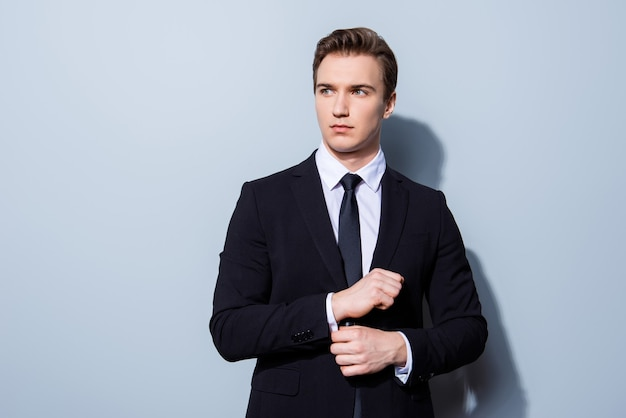 Banchiere giovane uomo d'affari bello in un vestito sta riparando i suoi gemelli, si trova su uno spazio di luce pura. così maturo e virile, caldo e sicuro di sé