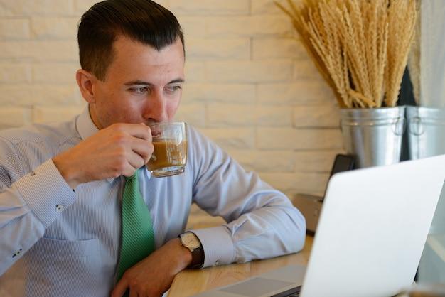 Giovane uomo d'affari bello che beve caffè mentre si lavora presso la caffetteria