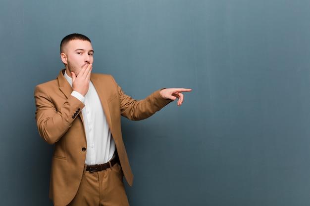Giovane uomo d'affari bello sentirsi felice, scioccato e sorpreso, coprendo la bocca con la mano e indicando lo spazio laterale della copia contro il piano