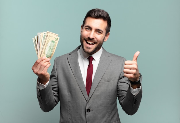 Giovane imprenditore bello sentirsi orgoglioso, spensierato, fiducioso e felice, sorridendo positivamente con i pollici in su