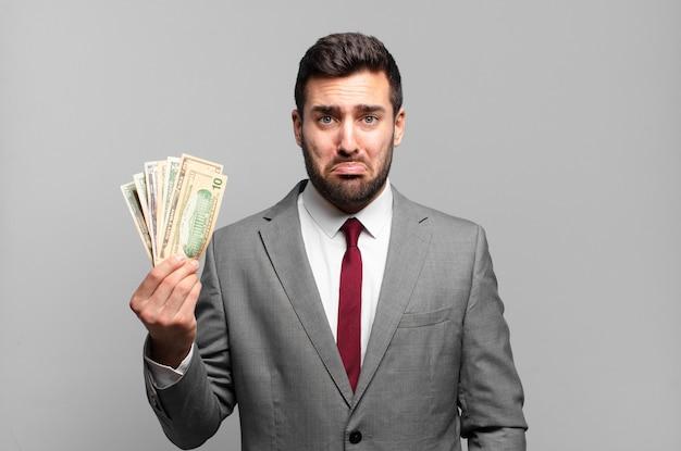 Giovane uomo d'affari bello che si sente triste e piagnucoloso con uno sguardo infelice, piangendo con un atteggiamento negativo e frustrato. bollette o concetto di denaro