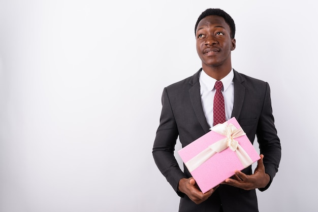 Contenitore di regalo bello giovane della tenuta dell'uomo d'affari contro bianco