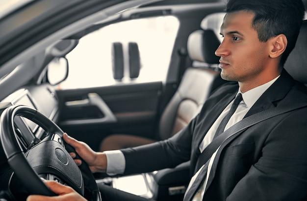 Il giovane uomo d'affari bello è seduto in un'auto di lusso. l'uomo serio in vestito sta guidando.
