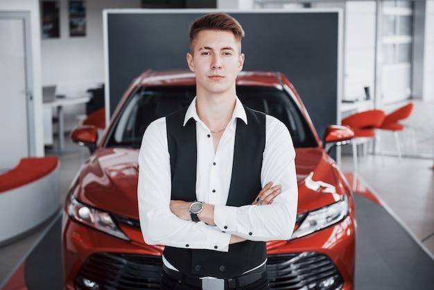 Un giovane uomo d'affari bello è in piedi vicino alla macchina.