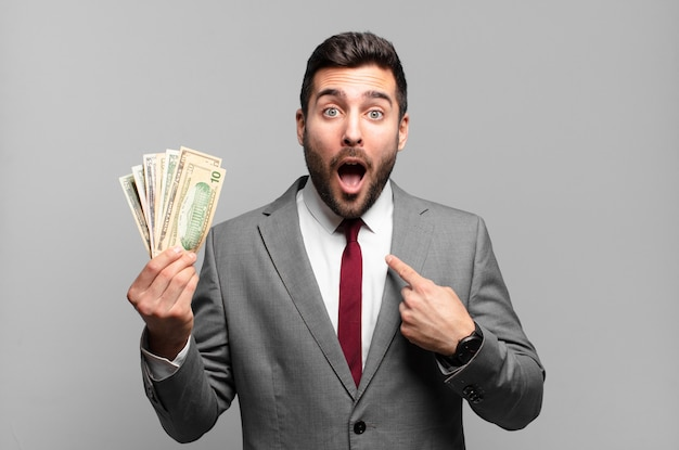 Giovane uomo d'affari bello che sembra scioccato e sorpreso con la bocca spalancata, indicando se stesso. bollette o concetto di denaro