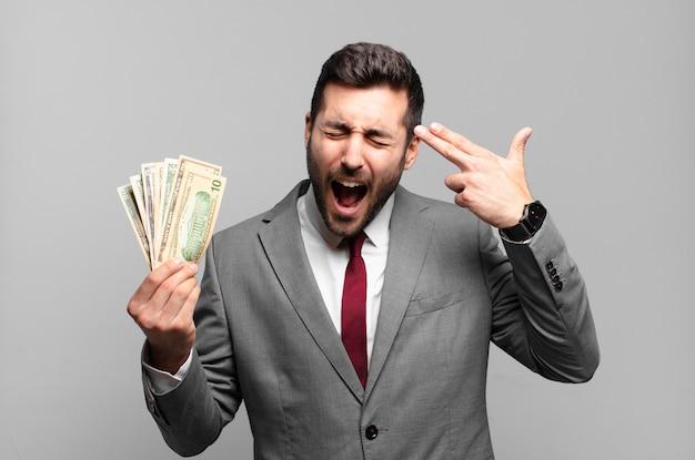 Giovane uomo d'affari bello che sembra infelice e stressato, gesto suicida che fa il segno della pistola con la mano, indicando la testa. bollette o concetto di denaro