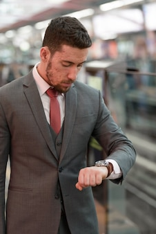 Giovane uomo d'affari bello che osserva orologio alla stazione ferroviaria