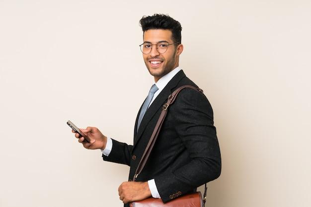 Giovane uomo bello dell'uomo d'affari sopra la parete isolata