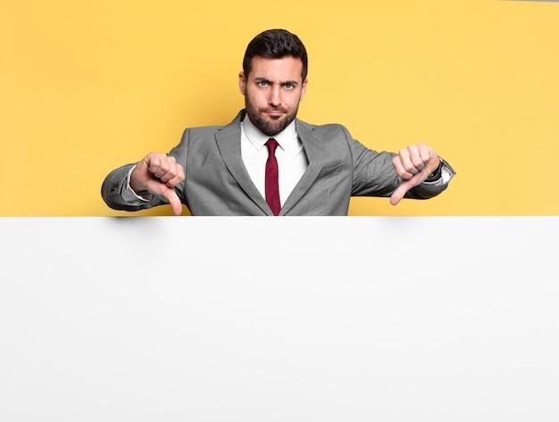 Giovane uomo d'affari bello che indica o mostra un posto vuoto al tuo concetto