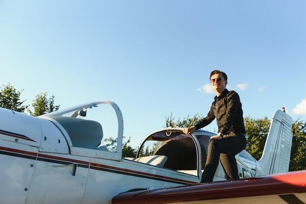 Giovane uomo d'affari bello che sta vicino all'aereo privato