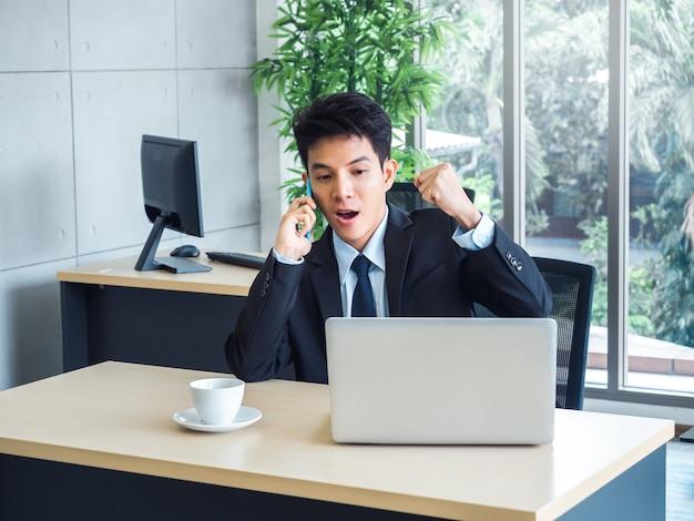 Giovane uomo d'affari bello in vestito che alza il pugno con eccitante e scioccante mentre chiama con il suo telefono cellulare e guarda il computer portatile sulla scrivania in ufficio con sensazione di vincitore e festeggia