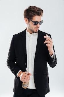 Giovane uomo d'affari bello in occhiali da sole che tengono bottiglia di birra e fumo di sigaretta sul muro grigio