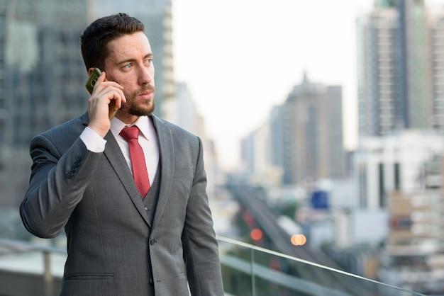 Giovane uomo d'affari bello che parla sul telefono cellulare a
