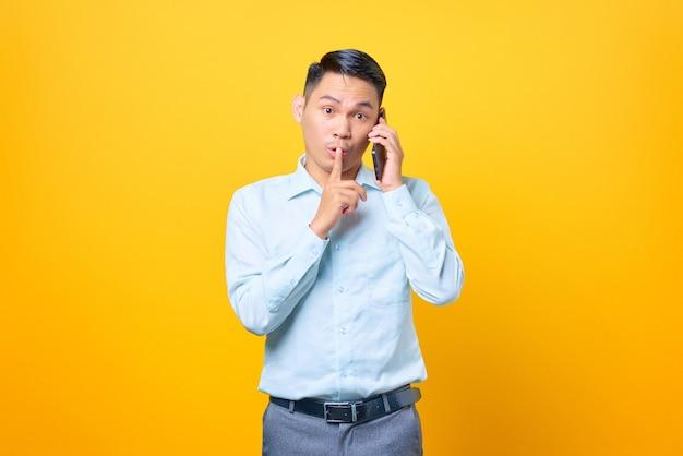 Giovane uomo d'affari bello che parla su smartphone e fa un gesto di silenzio su sfondo giallo