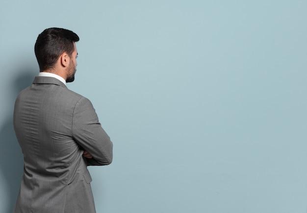 Giovane uomo d'affari bello pensare o dubitare. confrontando le opzioni