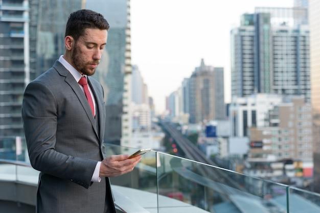 Bel giovane uomo d'affari utilizzando il telefono cellulare al rooft