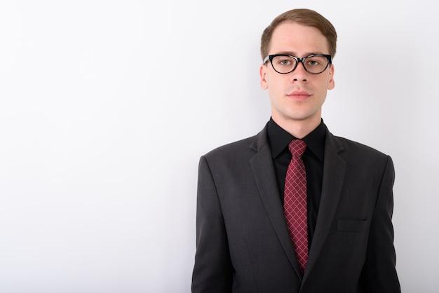Vestito da portare del giovane uomo d'affari bello sulla parete bianca