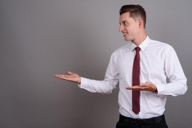 Giovane uomo d'affari bello che indossa camicia bianca e cravatta rossa su grigio