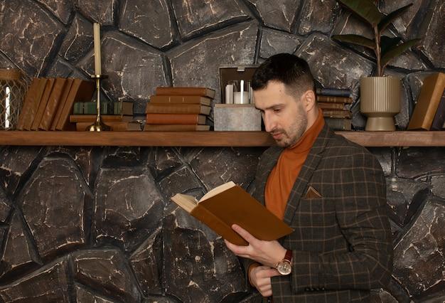 Giovane uomo d'affari bello con la barba nel libro di lettura del vestito?