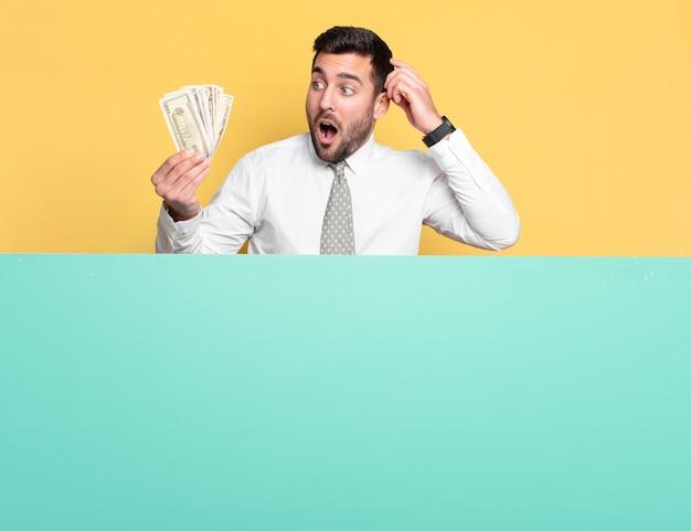 Bel giovane uomo d'affari con banconote in dollari. concetto di ricchezza