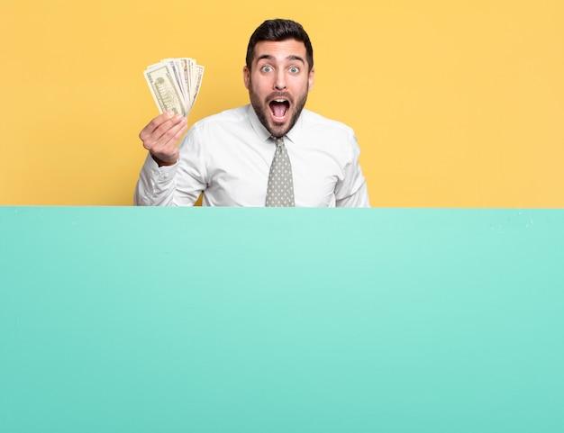 Giovane uomo d'affari bello con banconote in dollari. concetto di ricchezza