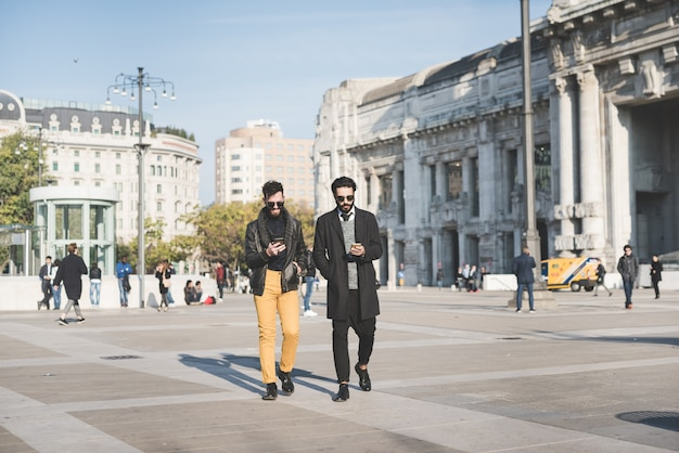 Giovani uomini barbuti caucasici bei dei capelli marroni che camminano nella città