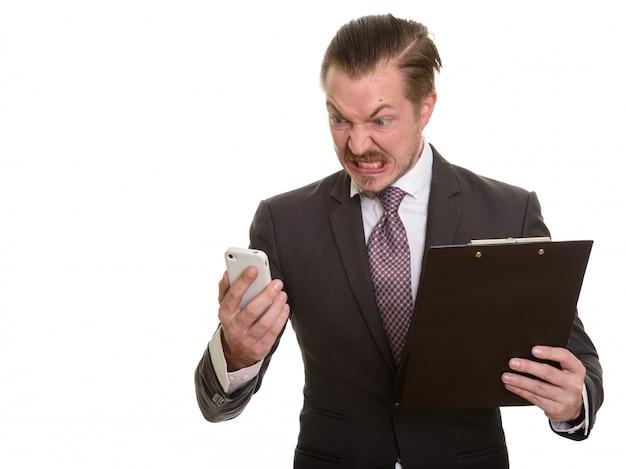 Giovane uomo d'affari caucasico bello che sembra arrabbiato mentre si utilizza il telefono cellulare e tenendo appunti