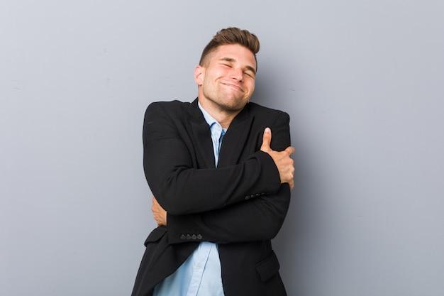 Abbracci di giovane uomo caucasico bello, sorridente spensierato e felice.
