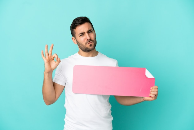 Giovane uomo caucasico bello isolato su sfondo blu con in mano un cartello vuoto e facendo segno ok
