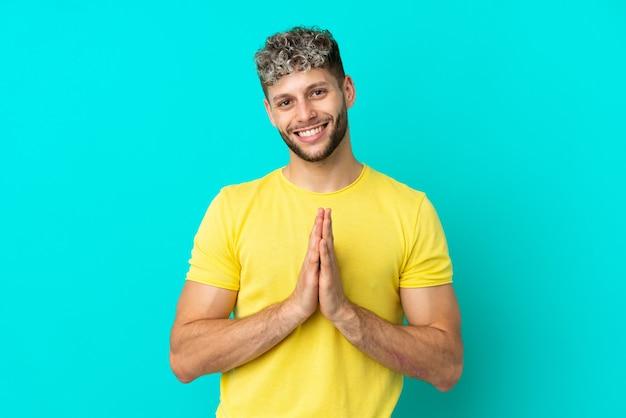 Il giovane uomo caucasico bello isolato su fondo blu tiene insieme il palmo. la persona chiede qualcosa
