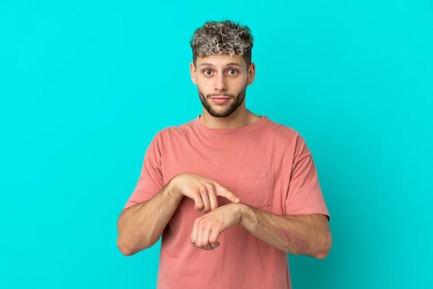Giovane uomo caucasico bello isolato su sfondo blu che fa il gesto di essere in ritardo
