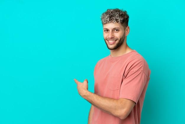 Giovane uomo caucasico bello isolato su sfondo blu che punta indietro