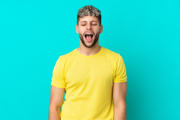 Giovane uomo caucasico bello isolato su sfondo blu che grida in avanti con la bocca spalancata