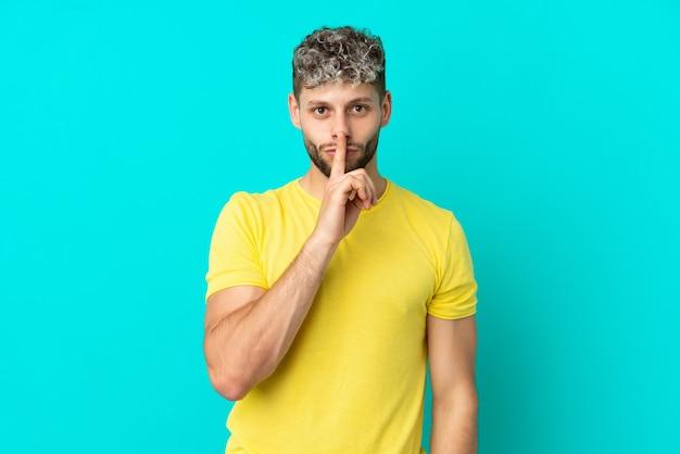 Giovane uomo caucasico bello isolato su sfondo blu che mostra un segno di gesto di silenzio mettendo il dito in bocca