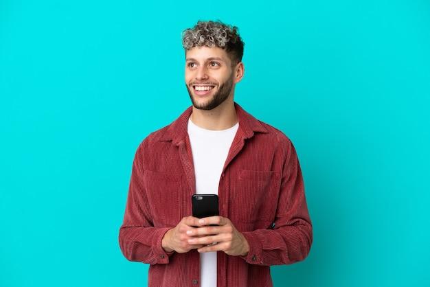 Giovane uomo caucasico bello isolato su sfondo blu utilizzando il telefono cellulare e guardando in alto